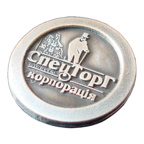 Stamped badge with the logo of the corporation SpetsTorg
